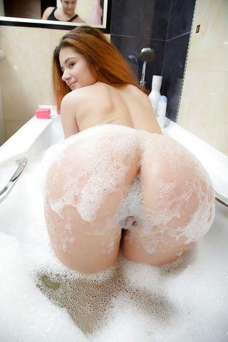 Сисястая рыжая стерва с упругой попкой мастурбирует под душем