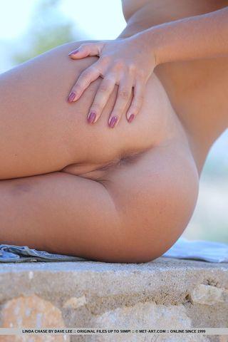 Худая девушка  на пляже показывает свои маленькие дойки