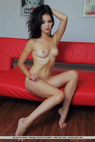 Грудастая девушка на рабочем диване показывает свою розовую вагину