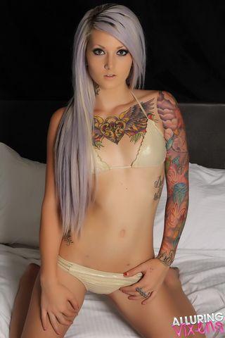 Татуированная блондинка  в бикини на кровати позирует фотографу