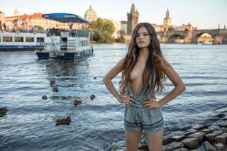Длинноволосая девушка с голыми сиськами села на улице на шпагат