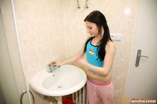 Худая брюнетка в туалете, сняв трусики, ласкает клитор пальцами
