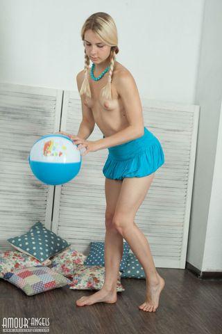 Молодая блондинка с мячмком в руках демонстрирует бритую промежность