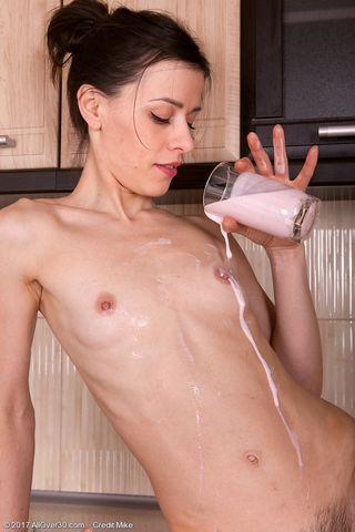 Брюнетка позирует на кухне и снимает стринги, после чего проливает йогурт на волосатую пилотку