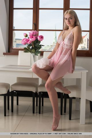 Блондинка сидит на  большом столе и большим пером ласкает небольшую грудь и волосатую пилотку