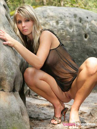 Блондинка в сексуальном пеньюаре позирует на больших камнях и показывает пикантные места крупным планом