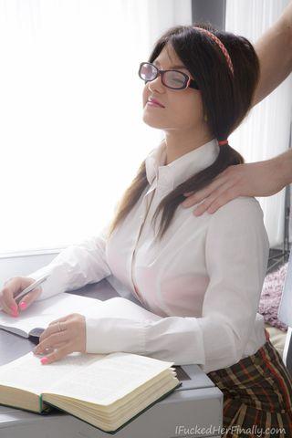 Брюнетка в очках обеими руками сжимает грудь и берет длинный пенис за щеку перед вебкамерой