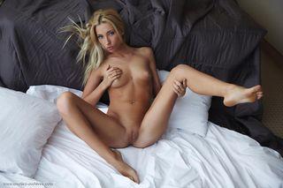 Худая блондинка с большой грудью лежит на белой постели и имеет себя в лысую киску пальцами