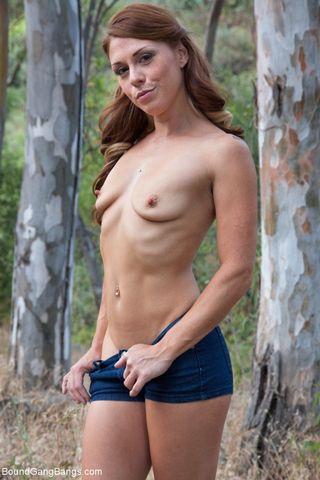 Рыжеволосая деваха снимает в лесу стринги и пальцами дергает себя за соски и пальцами трет кремовую щель