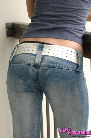 Брюнетка задирает футболку и вставляет пальцы в киску, не снимая брюк крупным планом