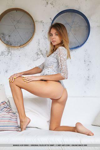 Блондинка лежит на белоснежном диване и шлепает себя по аппетитным ягодицам перед вебкой