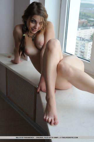 Девушка сидит совершенно голой возле окна и показывает волосатую пилотку крупным планом перед вебкой