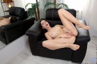брюнетка с красивой грудью лежит в кожаном кресле и демонстративно пальцами трет анальную и вагинальную щели