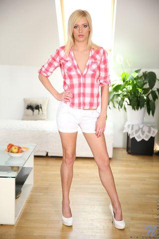 Классная блондинка в клетчатой рубашке разводит ноги около дивана и хвастается розовыми дырочками