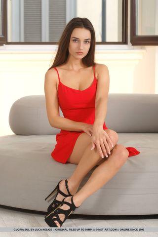 Молодая красотка снимает красное платье и бес стеснений показывает упругую грудь большого размера