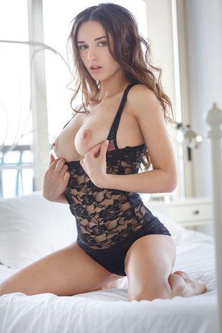 Страстная модель с большими сиськами обнажается на белоснежной постели и демонстрирует аппетитную попку