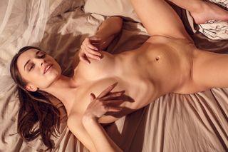 Стройная девушка с красивой грудью большого размера остается в одной лишь маске и позирует на постели